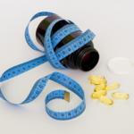 Foto de uma fita métrica enrolada. O frasco está aberto e tem algumas cápsulas de remédio espalhadas.