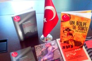Foto com diversos livros dispostos em pé e na horizontal com a bandeira da Turquia entre eles.